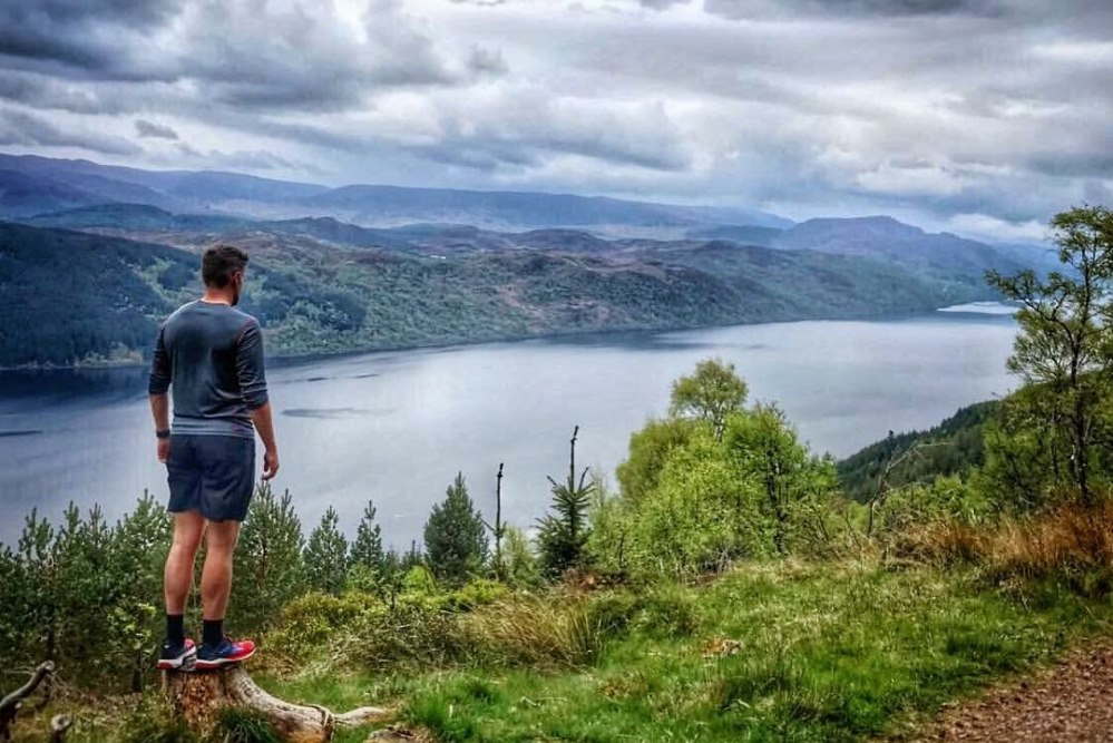Hiker on the Great Glen Way looking over Loch Ness in the Scottish Highlands