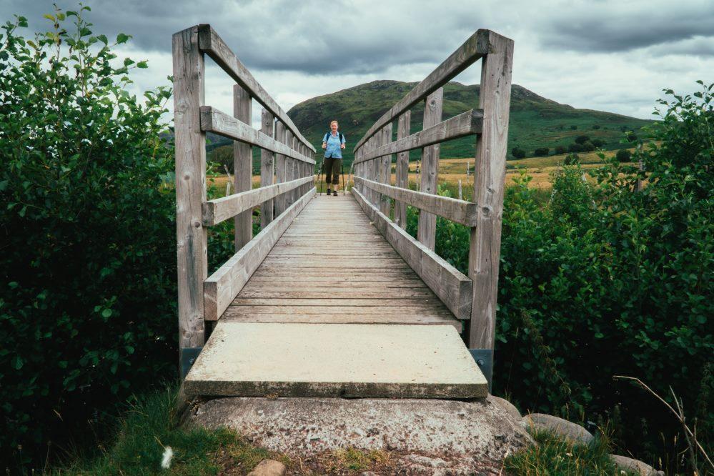 Walker crossing a bridge on the South Loch Ness Trail