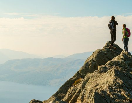 two woman atop a hill hiking safely up a mountain in the Scottish Highlands