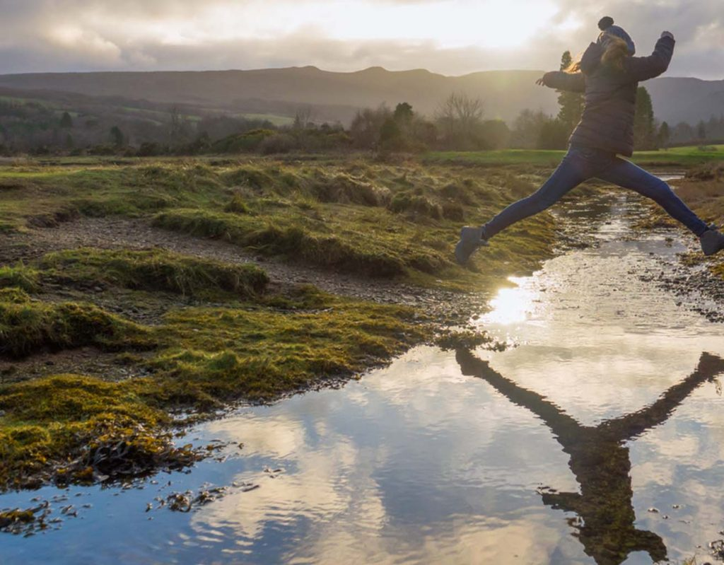 A woman jumps across a stream in the Highlands.