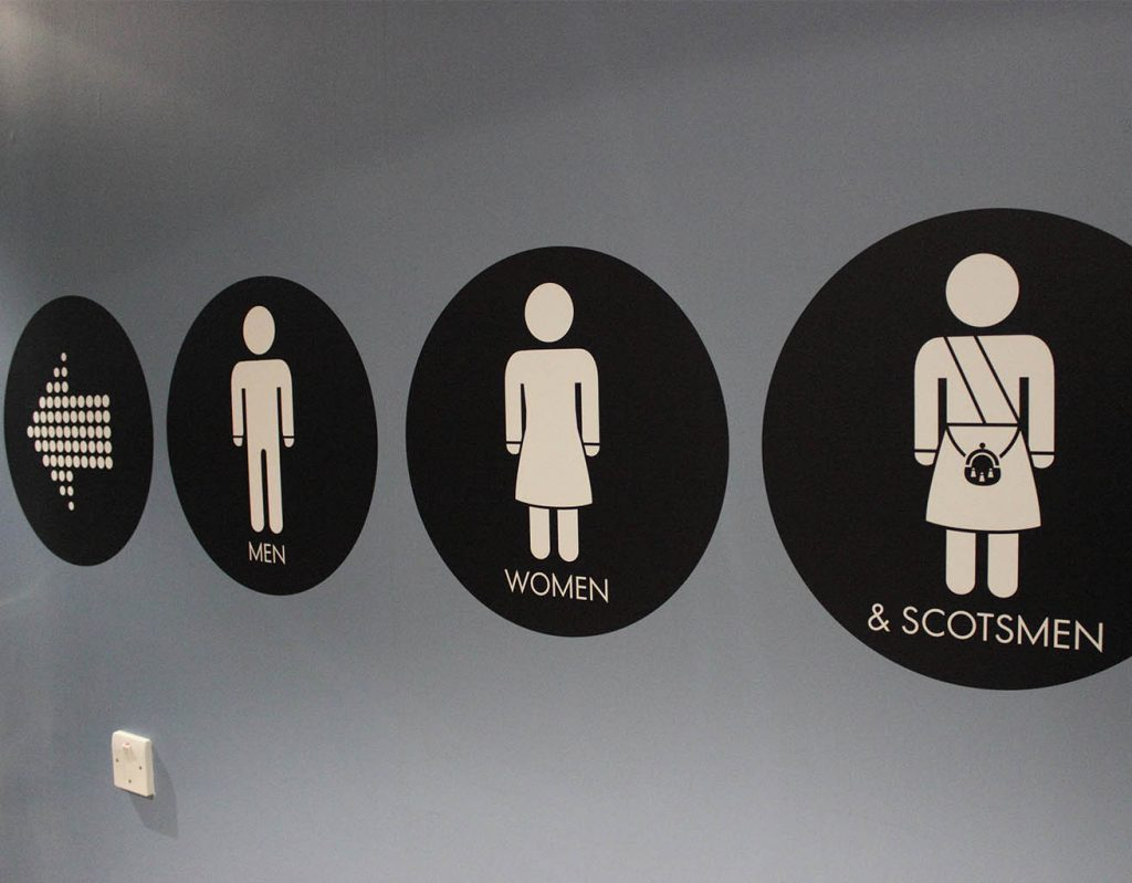 A Scottish sign for the toilets, including an image of a man in a kilt.