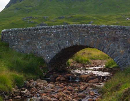 A small tent by an old stone bridge in the Scottish Highlands