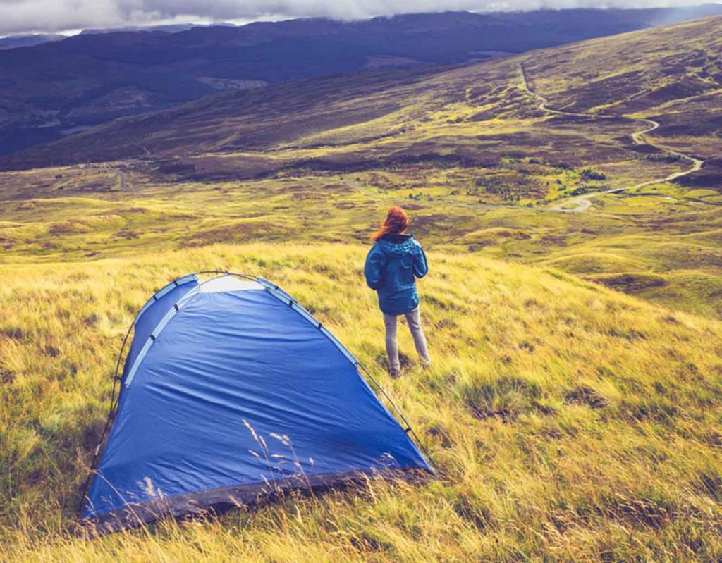 a woman stands next to her tent in the wilderness of the Scottish Highlands