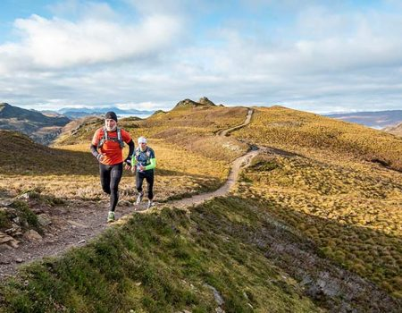 two people running in the highlands