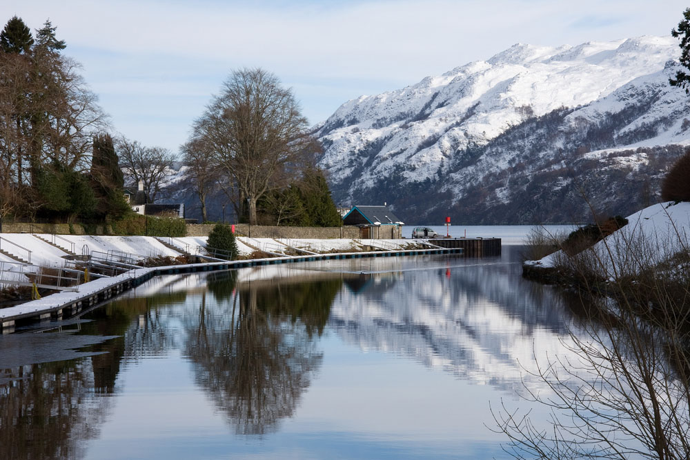 The Caledonian Canal going into Loch Ness on a snowy winters day with snowy mountains in the background