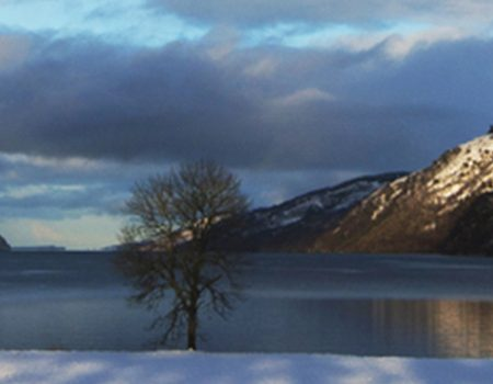 Snowy mountains cocooning Loch Ness