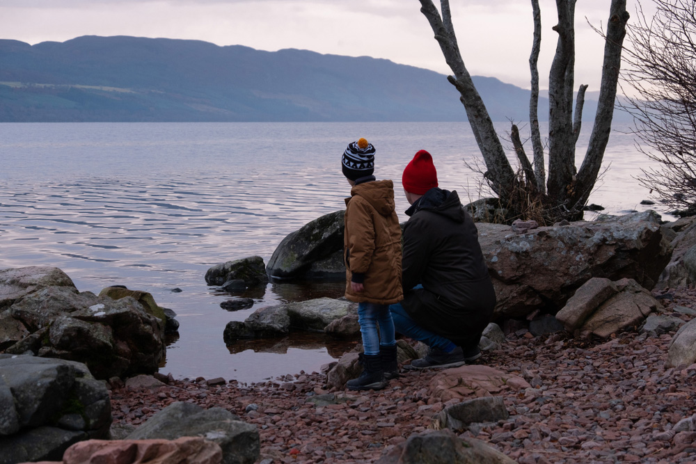 People in warm winters clothes on the banks of a loch in Scotland